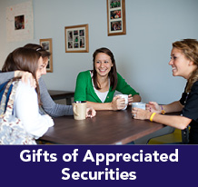 Rollover image of students at a table talking. Link to Gifts of Appreciated Securities.